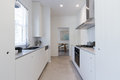 Renovated white galley style kitchen in modern apartment Royalty Free Stock Photo