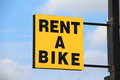 Rent a bike sign on blue sky background Stock Images