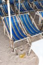 Rental beach canvas chairs and white table on natural white sand Royalty Free Stock Photo