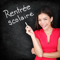 Rentree scolaire french teacher back to school written in on blackboard by woman holding chalk smiling happy woman Stock Image