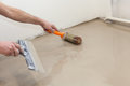 Repair work. Pouring floors in the room. Fill screed floor repair and furnish. Worker align cement with roller Royalty Free Stock Photo