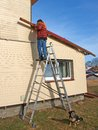 Repairing house man on aluminum folding ladder screw roof edging Stock Photo