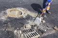 Repairing sewer manhole utilities worker cover in the road Stock Images