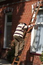 Repairman climbing ladder Royalty Free Stock Photo