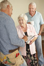 Repairman giving senior couple estimate for repair Stock Photos