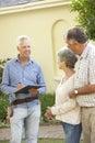 Repairman giving senior couple estimate for roof repair Stock Photos