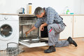 Repairman Repairing Dishwasher With Screwdriver In Kitchen Royalty Free Stock Photo