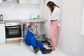 Repairman repairing pipe while woman in the kitchen young sink standing Stock Photography