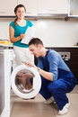 Repairman repairing a washing machine for housewife Stock Photography
