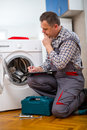 Repairman is repairing a washing machine on the white background Royalty Free Stock Photo