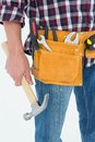 Repairman wearing tool belt while holding hammer close up of male on white background Stock Photo