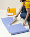 Repairs in the house woman unrolling wallpaper Royalty Free Stock Photo