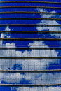 Repetitive horizontal louvers and reflective sky exterior facade with multiple windows reflecting a blue with clouds Stock Images