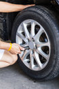 Replacing lug nuts by hand while changing tires on a vehicle Stock Photography
