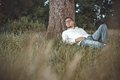 Repose young handsome man on grass against a tree gorgeous guy lie down on meadow in nature outdoors outside Stock Photo