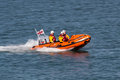 Rescue boat in the dublin bay close to the city of dún laoghair lifeboat with three people sea cruising through harbour Royalty Free Stock Images