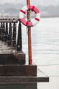 The rescue hoop life buoy hanging on a post at pier by riverside Stock Photos