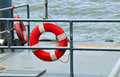 Rescue life buoy hanging on a post at the pier by the riverside Stock Photography
