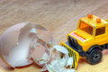 Rescue truck or bulldozer clearing away debris a toy with some broken eggshells moving them Stock Image