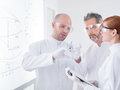 Reseachers preparing an injection close up of tree people in a chemistry lab with a whiteboard on the background Royalty Free Stock Photography
