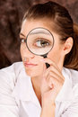Researcher looking through magnifier glass pretty female Stock Image