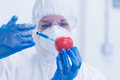 Researcher in protective suit injecting tomato at lab close up of a a the Royalty Free Stock Photos