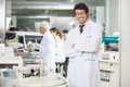 Researcher standing arms crossed portrait of smiling male in laboratory near centrifuge Royalty Free Stock Photo