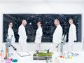 Researcher team in laboratory sidel view of five confident people a chemistry lab around lab tools leafs and colorful liquids with Stock Image