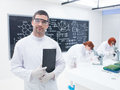 Researchers in a chemistry lab close up of scientist smiling with two women the background chemically analysing under microscope Royalty Free Stock Photo