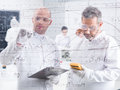 Researchers lab data analysis close up of two in a writing formulas on a transparent board and scanning results with another two Stock Photography