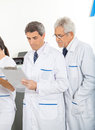 Researchers reading clipboard male in laboratory Stock Photo