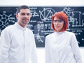 Researchers smiling in a laboratory close up of two chemistry lab with blackboard on the background Royalty Free Stock Image