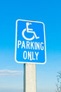 Reserved parking sign a indicating a space for disabled people blue sky as a background Royalty Free Stock Photography