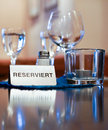 Reserved restaurant table polished with glasses for water and wine and one with candle and white sign with black text Royalty Free Stock Images