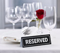Reserved table at romantic restaurant setting with roses plates and cutlery Stock Photography