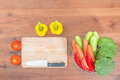 Resh vegetables and knife on cutting board on wood table Royalty Free Stock Photo