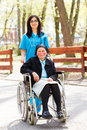 Residential care beautiful doctor nurse in blue coat walking a kind elderly lady in wheelchair in park Stock Image