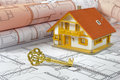 Residential house and golden key over building plan Royalty Free Stock Photography
