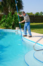 Residential pool cleaning service man working on a sparkling clean pool brushing the side clean Stock Photography
