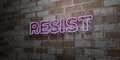 RESIST - Glowing Neon Sign on stonework wall - 3D rendered royalty free stock illustration