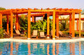 Resort swimming pool, wood pergola and deck chairs Stock Image