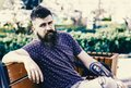 Rest and relax concept. Bearded man with fresh haircut relaxing, urban background. Hipster enjoy sunny day in park. Man Royalty Free Stock Photo