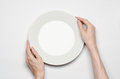 Restaurant and Food theme: the human hand show gesture on an empty white plate on a white background in studio isolated top view Royalty Free Stock Photo