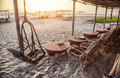 Restaurant in goa on the beach with wooden chairs and tables at sunset india Royalty Free Stock Image