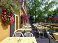 Restaurant outdoor patio with colorful hanging floral baskets Royalty Free Stock Images