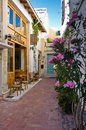 Restaurant in shade at the street of old medieval city and harbor Rethymno, Crete Stock Images