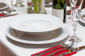 Restaurant table setting with plates wine glasses and silver cutlery Royalty Free Stock Photos