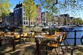 Restaurant tables lining the canals of Amsterdam during springtime, Netherlands Royalty Free Stock Photo