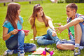 Restful college friends friendly teenagers spending free time on green lawn Royalty Free Stock Image