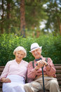 Restful couple happy seniors sitting on bench in the park and looking at camera Stock Photos